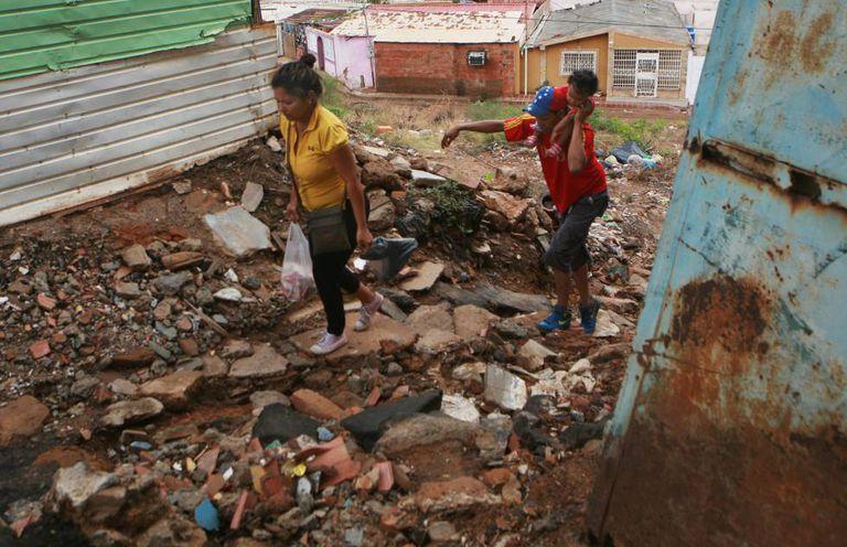 Dois venezuelanos entre entulho em Maracaibo.
