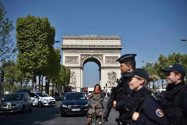 Policiais franceses patulham a Champs Élysées, em Paris, um dia após o atentado.