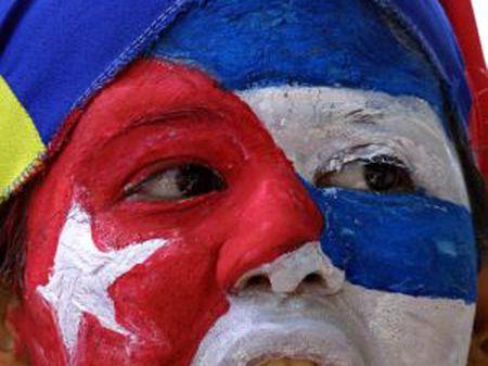 Uma mulher com a bandeira cubana pintada no rosto em frente à embaixada de Cuba na Venezuela.