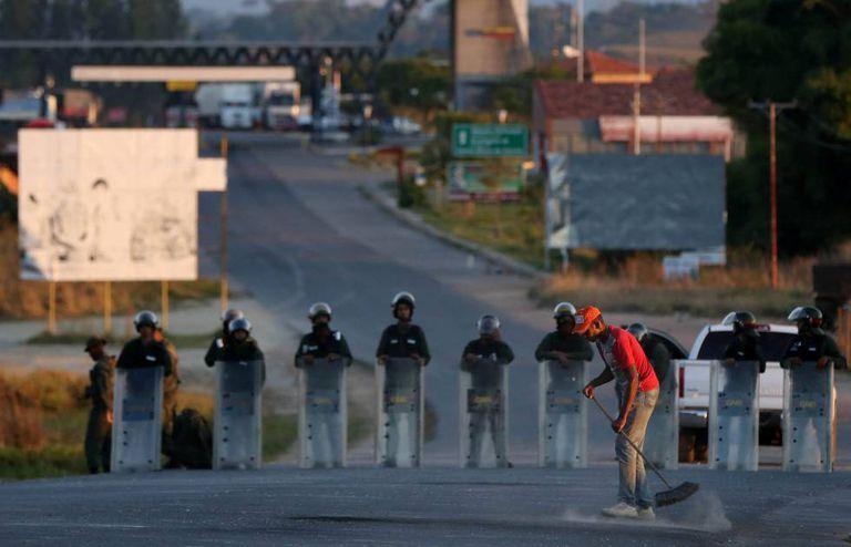 Uma barreira venezuelana perto da fronteira com Brasil, guardada pela Guarda Nacional Bolivariana.