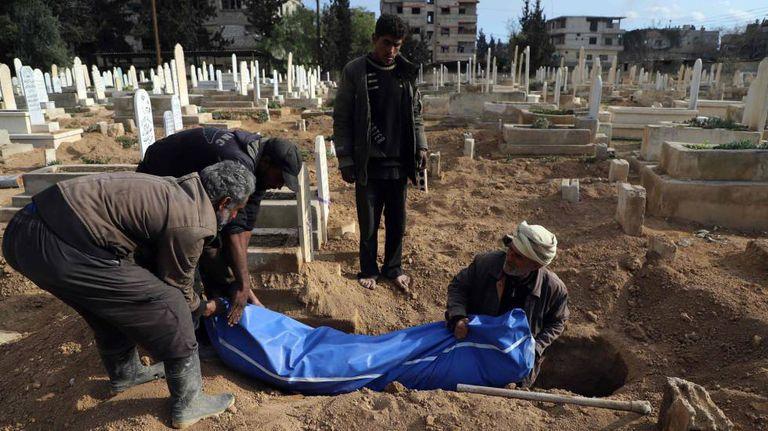 Sírios enterram um corpo em Guta, na quinta-feira