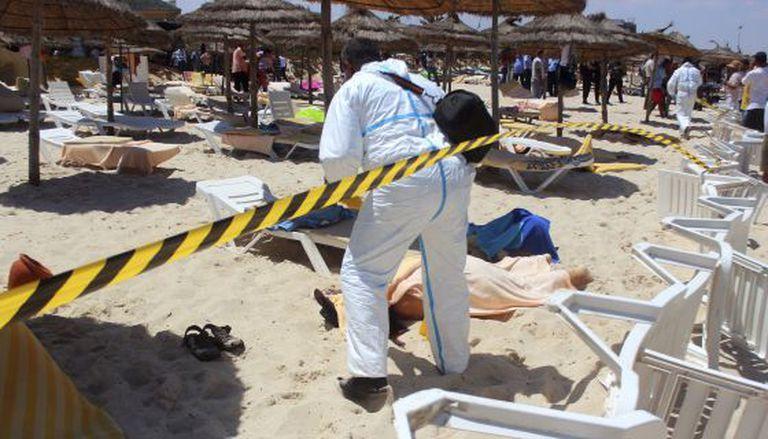 Um policial, ao lado de duas vítimas do ataque terrorista de sexta-feira em Sousse.