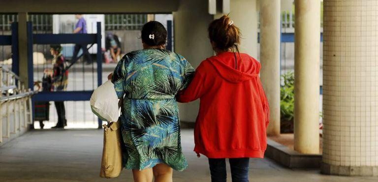 Menor que foi vítima de estupro coletivo deixa o Hospital Souza Aguiar, acompanhada da mãe.