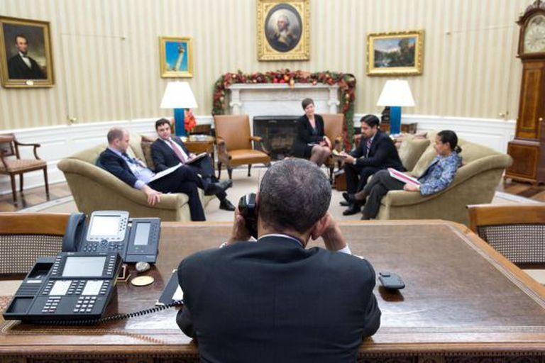 Barack Obama conversa por telefone com Raúl Castro no Salão Oval, na presença do Ben Rhodes e Ricardo Zúñiga, entre outros.