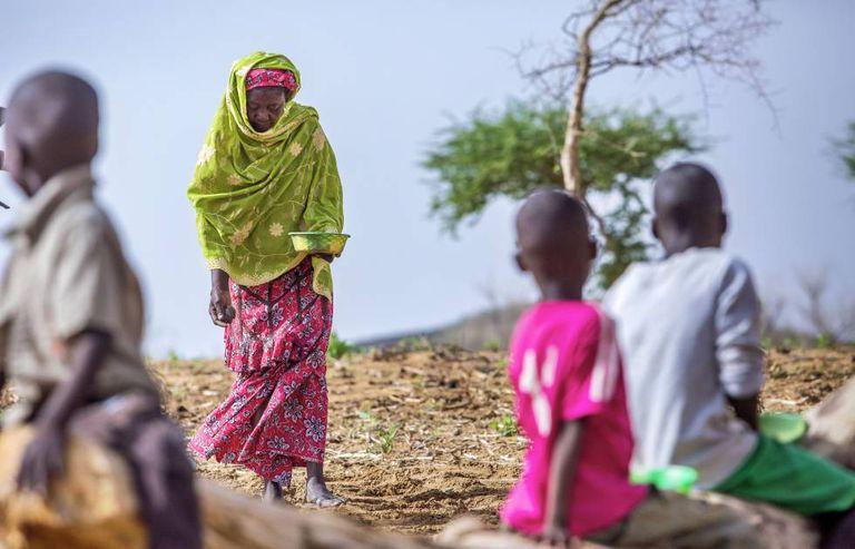Uma avó com seus netos em um campo de amendoins em Gafati (Níger)