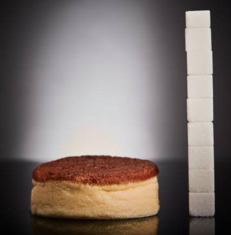 Um bolo ao lado da quantidade de açúcar que contém.