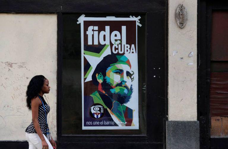 Uma mulher passa diante de um pôster de Fidel Castro na manhã deste sábado, em Havana, horas após o anúncio da morte do ex-presidente.