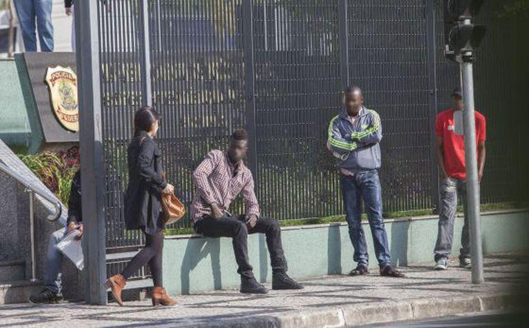 Imigrantes aguardam na porta da Superintendência da PF de São Paulo.
