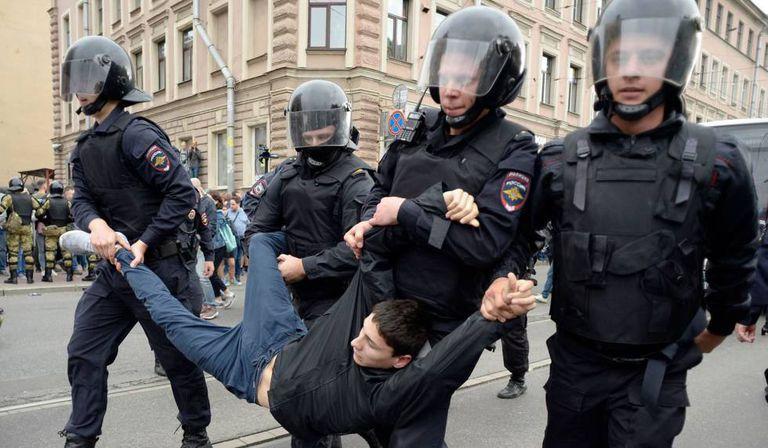 Um manifestante é preso por quatro policiais, neste domingo em San Petersburgo.