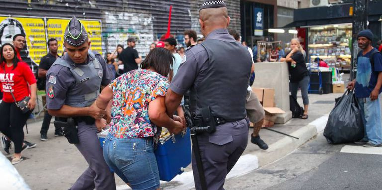 Policiais seguram vendedora ambulante.