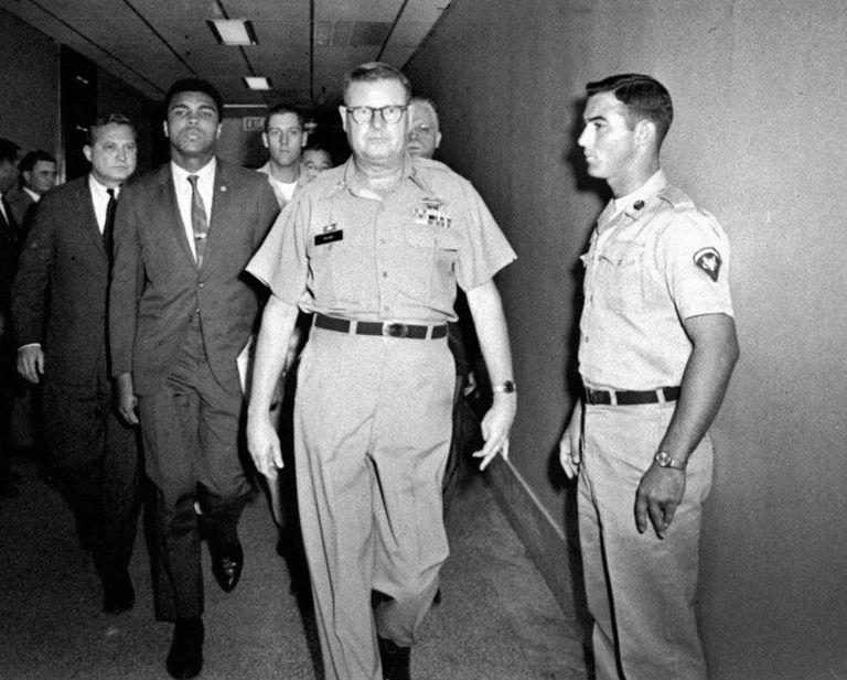 Muhammad Ali é escoltado pelo comandante do centro de recrutamento de Houston, em 1967, depois de ter se recusado a se alistar.