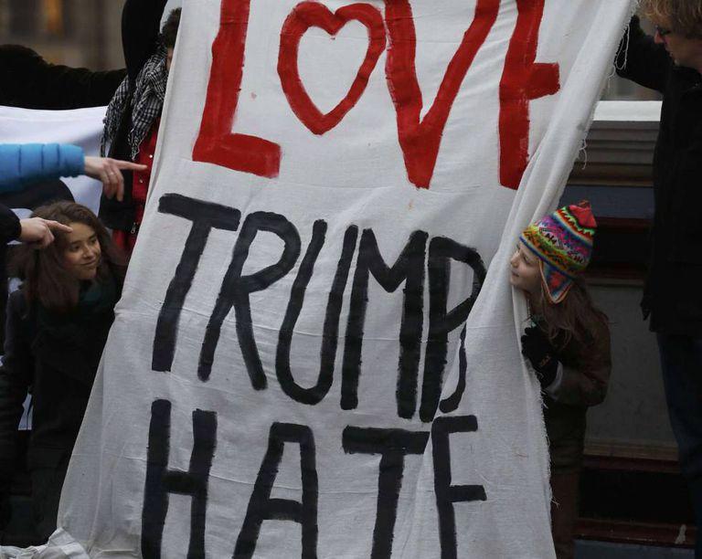 """Manifestantes seguram o cartaz com o trocadilho """"Love Trumps Hate"""" (O amor supera o ódio)."""