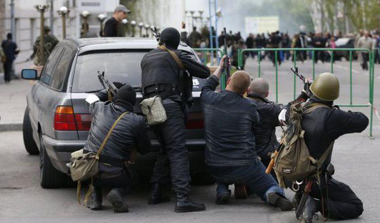 Um grupo de combatentes pró-russos se esconde atrás de um carro perto da sede da polícia de Luhansk, na Ucrânia.