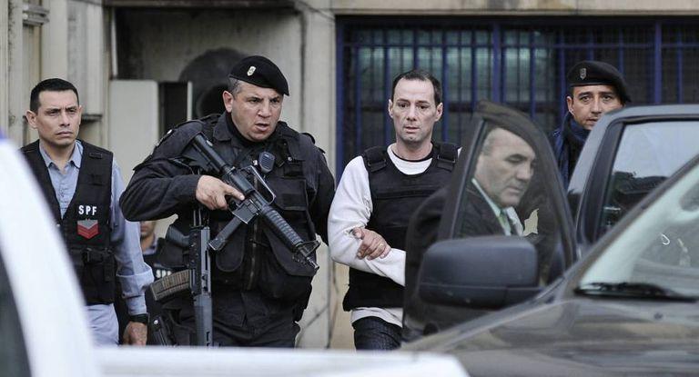 Escoltado, Martín Lanatta deixa o fórum depois de testemunhar, em agosto.