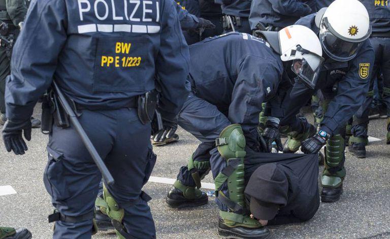A polícia detém um manifestante durante o protesto contra o AfD, em Stuttgart.