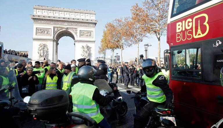 Manifestantes contra a subida dos combustíveis bloqueiam o passo de um ônibus turístico, neste sábado em Paris.