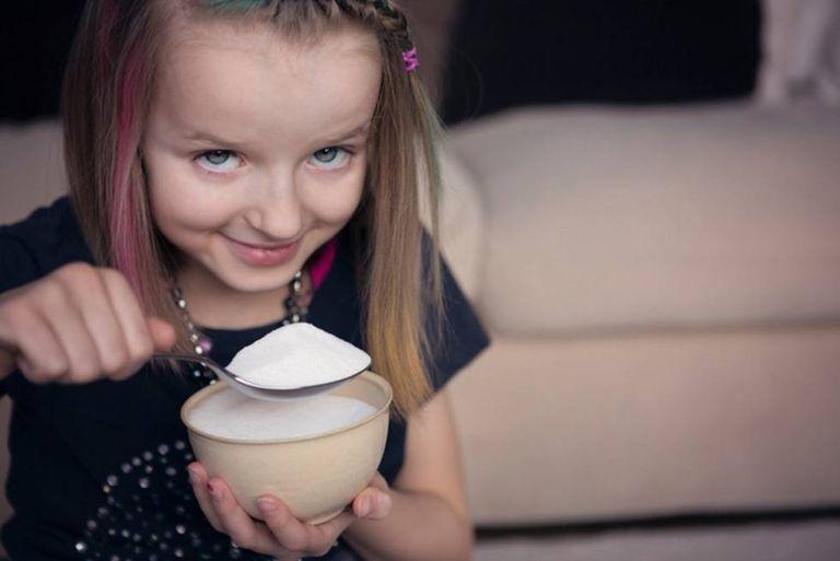 Criança come açúcar.