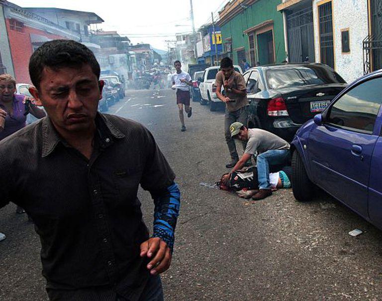 Um homem atende jovem baleado na segunda-feira durante um protesto em San Cristóbal, na Venezuela.