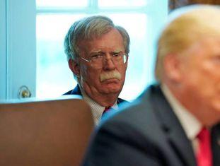 Trump com o assessor da Casa Branca, John Bolton, ao fundo.