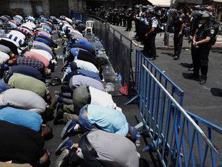 Fiéis palestinos oram diante da polícia israelense na porta de Damasco, em Jerusalém.