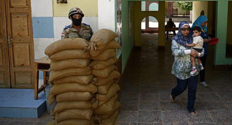 Uma mulher caminha depois de votar em al-Manial, um subúrbio do Cairo.