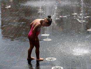 Menina se refresca em chafariz de Madri, durante uma onda de calor.