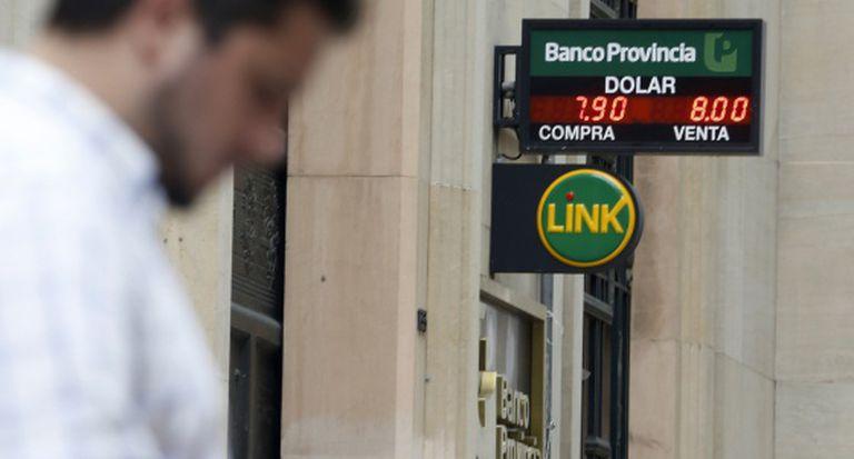 Um homem passa em frente a um banco na sexta-feira.
