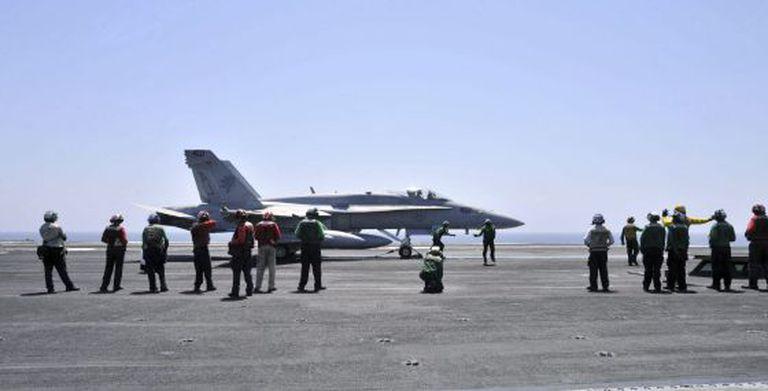 Membros da Marinha dos EUA guiando um avião Hornet F/A 18.