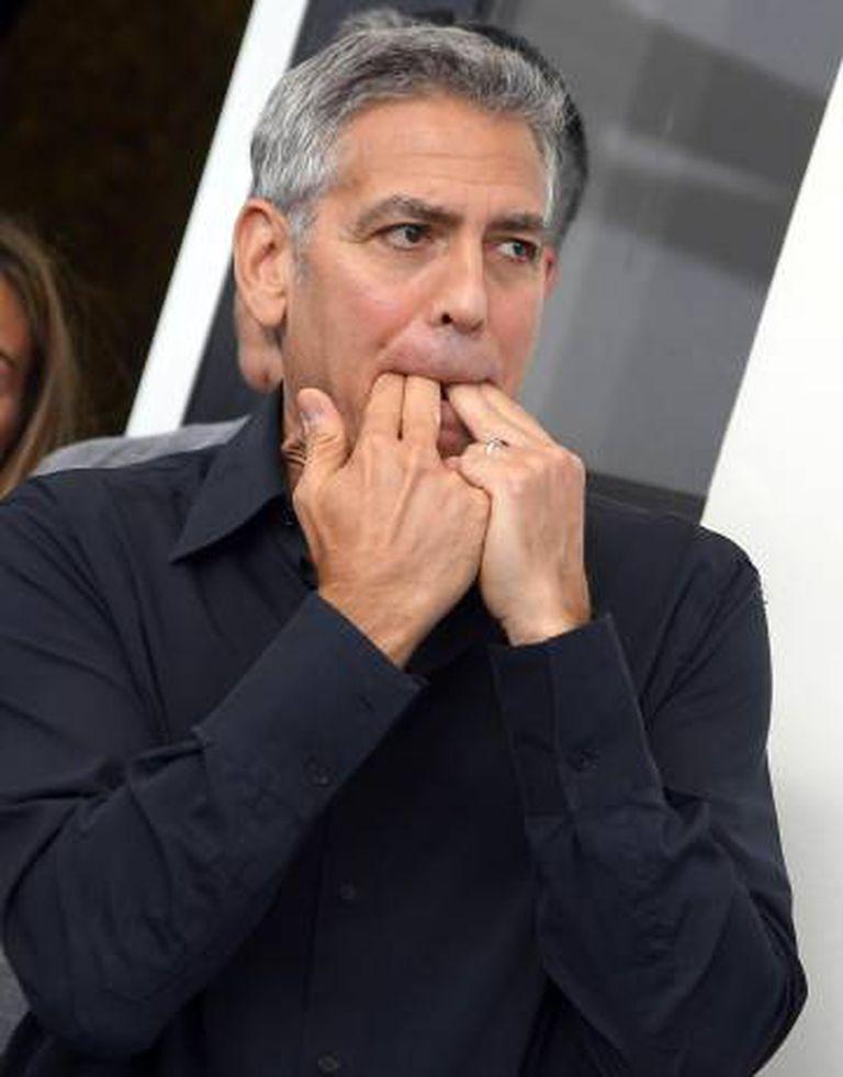 George Clooney assobia no posado ante os fotógrafos em Veneza.