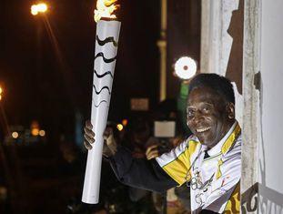 Pelé segura a tocha olímpica.