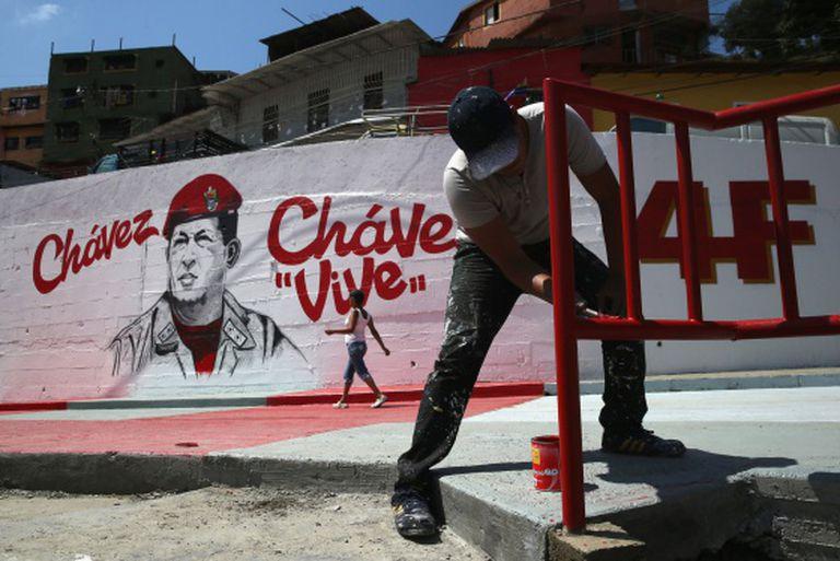 Homens pintando um mural em homenagem a Chávez.