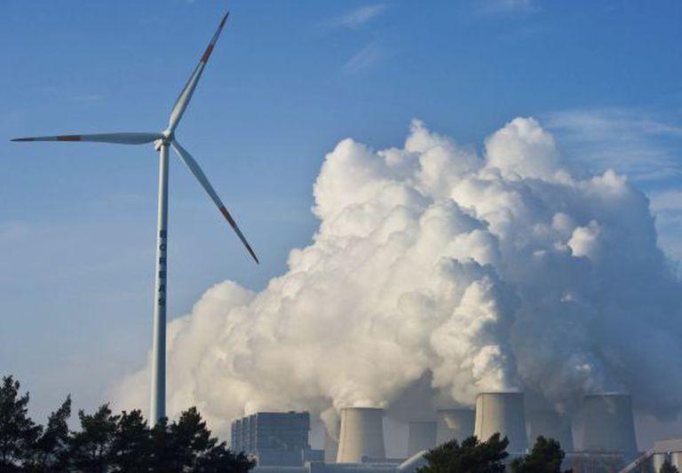 Uma turbina de energia eólica em frente a uma usina.