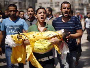 Um familiar leva o cadáver de Qassim Elwan, de quatro anos.