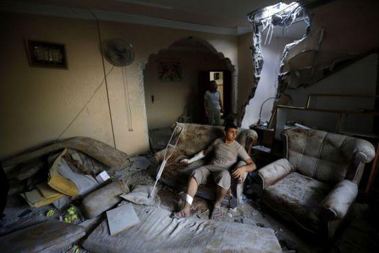 Um ferido palestino em sua casa destruída após um ataque de Israel sobre um campo de refugiados no norte de Gaza, em 10 de agosto de 2014.