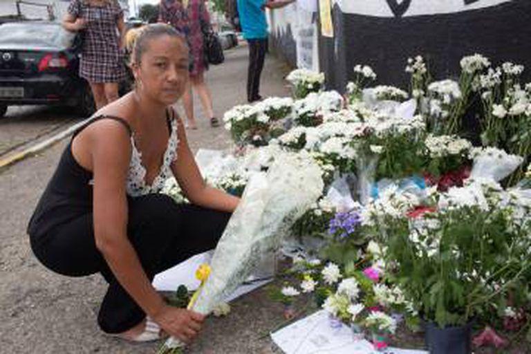 Fabiana Victor, mãe de uma das sobreviventes do massacre, deposita flores na escola de Suzano.