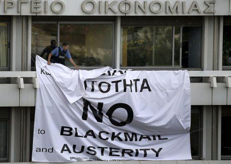Segurança tira faixa em protesto contra a austeridade, em Atenas.