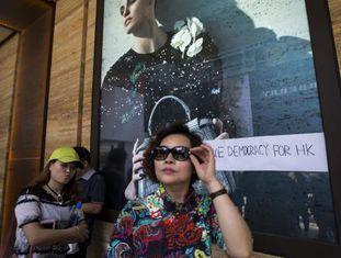 Mulher passa por loja com pichação pró-democracia.
