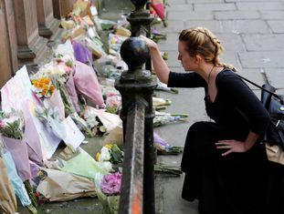 Uma mulher deposita flores pelas vítimas do atentado na Manchester Arena na terça-feira.