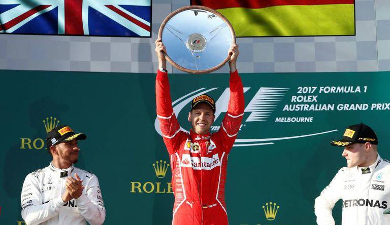 Sebastian Vettel (ao centro) comemora sua vitória no pódio, ao lado de Lewis Hamilton (à esq.), segundo colocado, e Valtteri Bottas, o terceiro.