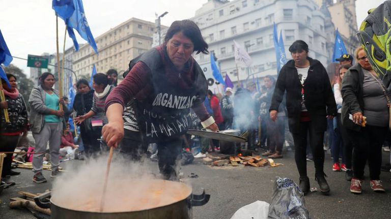 Uma mulher prepara comida em uma manifestação.