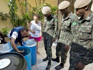 Solados e agente procuram larvas de Aedes aegypti