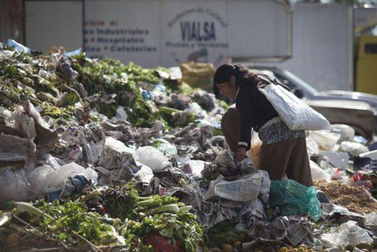 Mulher busca restos de alimentos na Cidade do México.