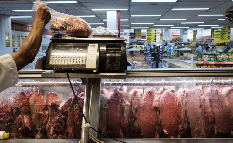 Funcionário pesa um pedaço de carne durante inspeção do Procon no Rio.