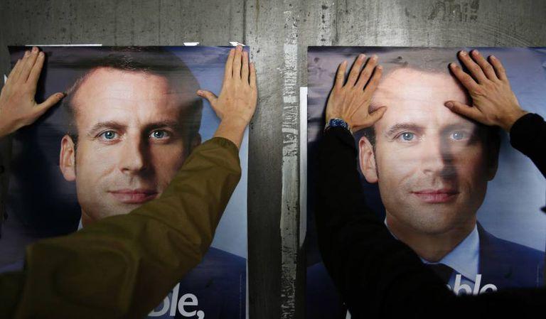 Um simpatizante de Macron cola um cartaz eleitoral na terça-feira, em Lille.