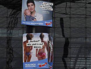 """Cartazes de campanha do AfD onde se lê: """"Qual é seu motivo para lutar pela Alemanha?"""" e """"Burcas? Nós preferimos biquínis""""."""