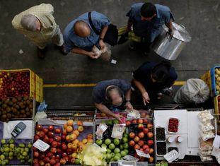 Clientes contam bolívares em um mercado de Caracas.