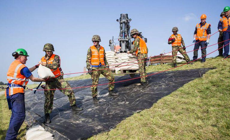 Vários soldados colaboram para reforçar um dique na Holanda.