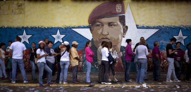 Fila em Caracas diante de um muro pintado com o rosto de Hugo Chávez.