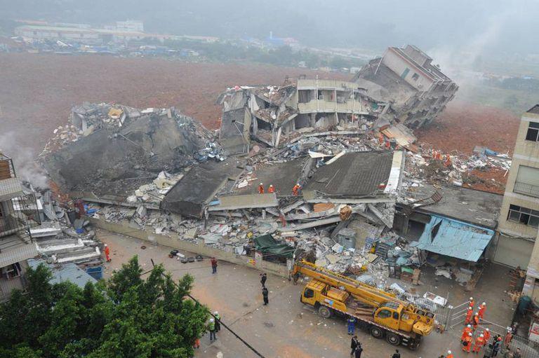 Equipe de resgate procuram sobreviventes entre prédios desabados.
