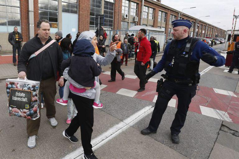 Passageiros e funcionários deixam o aeroporto internacional de Zaventem, nos arredores de Bruxelas, após as explosões no local.